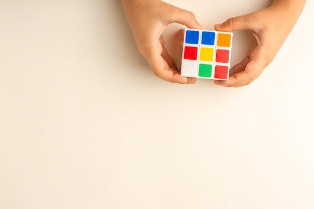 Вид сверху маленький ребенок играет с кубиком рубика на белом столе