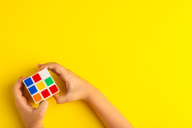 노란색 표면에 루빅스 큐브를 가지고 노는 상위 뷰 작은 아이