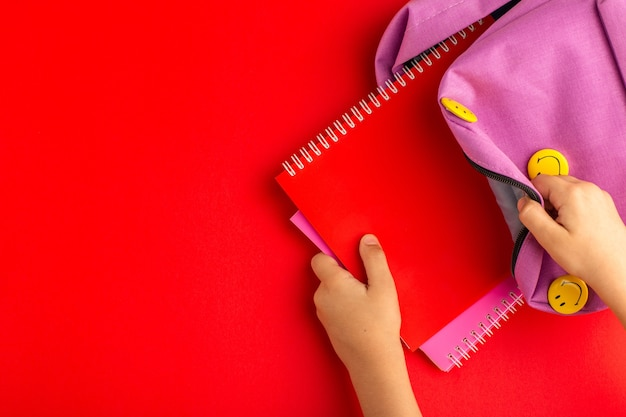 Top view little kid preparing for school taking copybook from bag on red surface