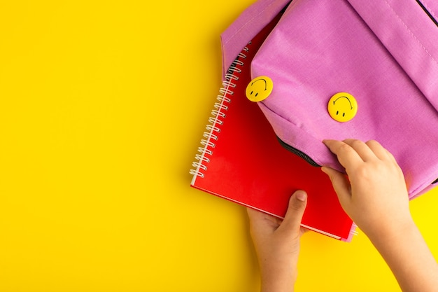 Top view little kid preparing for school taking copybook from bag on yellow surface