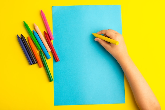 Top view little kid using colorful pencils on blue paper on the yellow surface