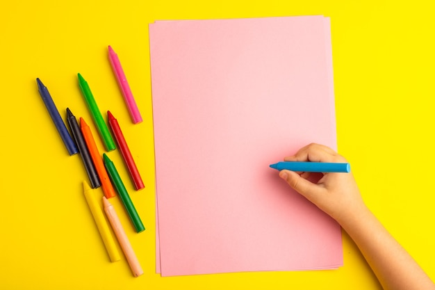 Top view little kid using colorful pencils on pink paper on the yellow surface