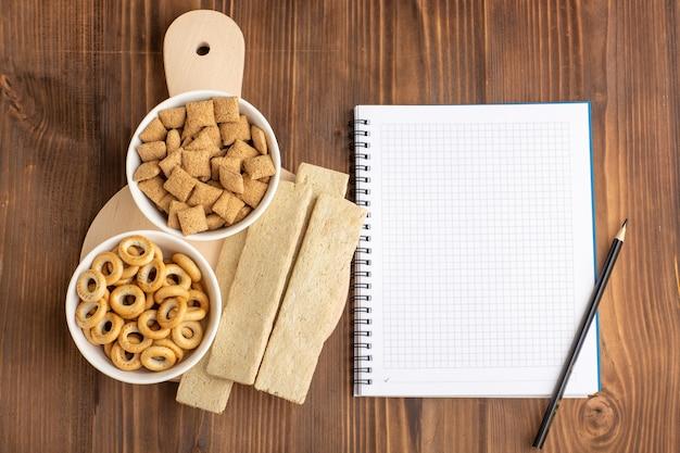 Вид сверху маленькое печенье в виде подушки с крекерами и блокнотом на коричневом столе