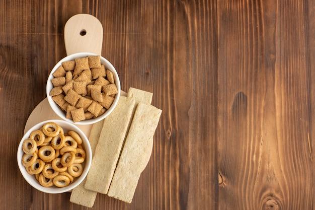 Vista dall'alto piccoli biscotti con cracker sulla scrivania marrone