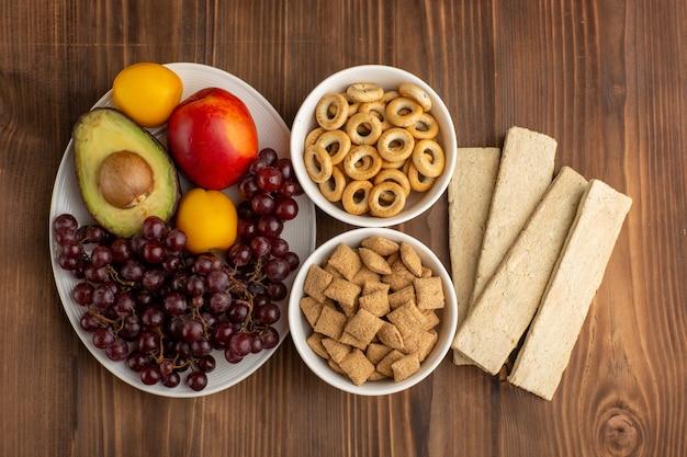 Vista dall'alto piccoli biscotti con cracker e frutta sulla scrivania marrone