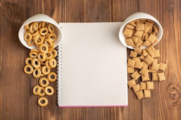 茶色の木製の机の上にクラッカーとトップビューの小さな枕クッキー