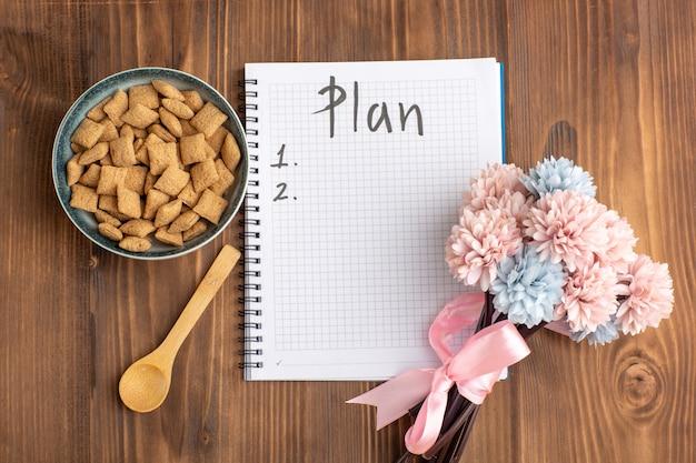 Vista dall'alto piccoli biscotti cuscino con blocco note e fiori sulla scrivania marrone