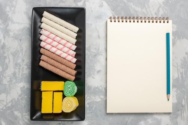 Vista dall'alto piccoli biscotti del tubo con marmellata d'arance e blocco note su sfondo bianco biscotto torta di zucchero torta dolce