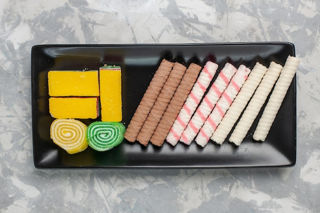 Vista dall'alto piccoli biscotti della pipa con marmellata sulla torta di torta dolce di zucchero biscotto bianco scrivania