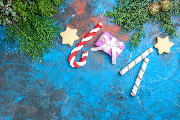 Vista dall'alto di piccoli regali con caramelle sulla superficie blu