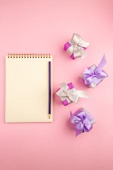 Vista dall'alto di piccoli regali con blocco note sulla superficie rosa