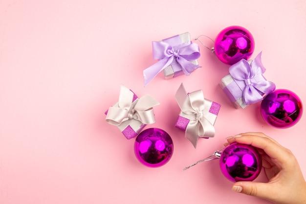 Vista dall'alto di piccoli regali con i giocattoli dell'albero di natale sulla superficie rosa