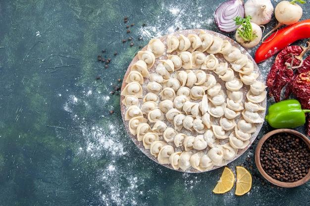 上面図暗い背景に小麦粉と野菜が入った小さな生餃子肉生地食品料理カロリー色焼き野菜ミール