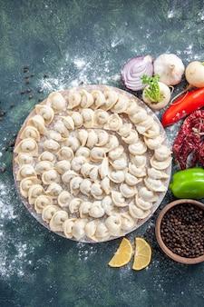 上面図暗い背景に小麦粉と野菜が入った小さな生餃子肉生地食品料理カロリー色野菜ミール