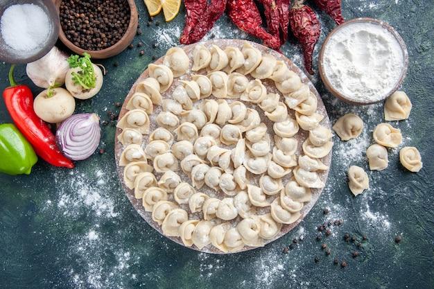 上面図暗い背景に小麦粉と野菜が入った小さな生餃子肉生地食品料理カロリー食事色焼き野菜