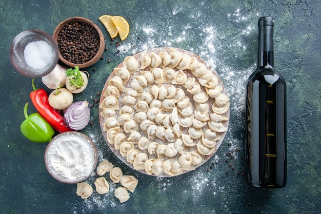 上面図暗い背景に小麦粉を入れた小さな生餃子肉生地食品料理カロリー食事色ワイン野菜