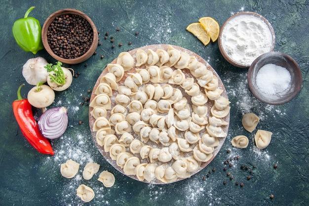 上面図濃い灰色の背景に小麦粉を入れた小さな生餃子生地の色食品食品料理肉カロリーミール