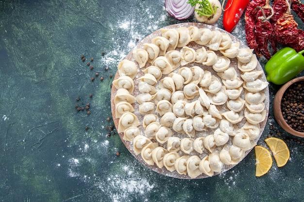 Vista dall'alto piccoli gnocchi crudi con farina e verdure su sfondo scuro pasta di carne piatto alimentare calorie colore pasto vegetale