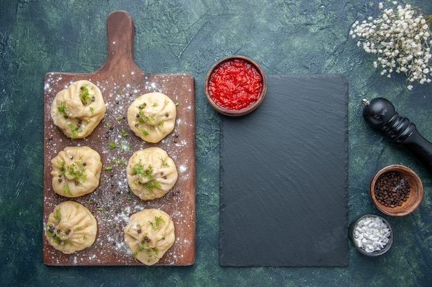 Top view little raw dumplings with meat inside on dark-blue surface dough dish cake meat dinner meal cooking
