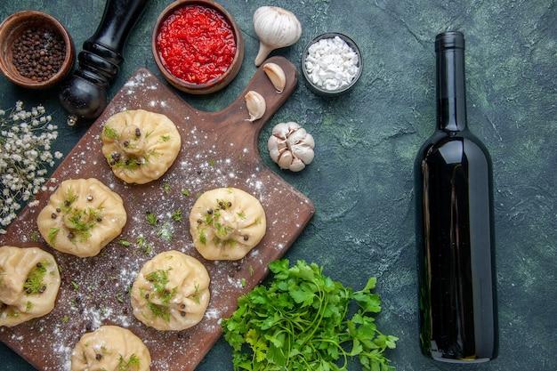 Vista dall'alto piccoli gnocchi crudi con salsa di pomodoro su sfondo blu scuro cucina cena pasta vino piatto pasto cucina carne
