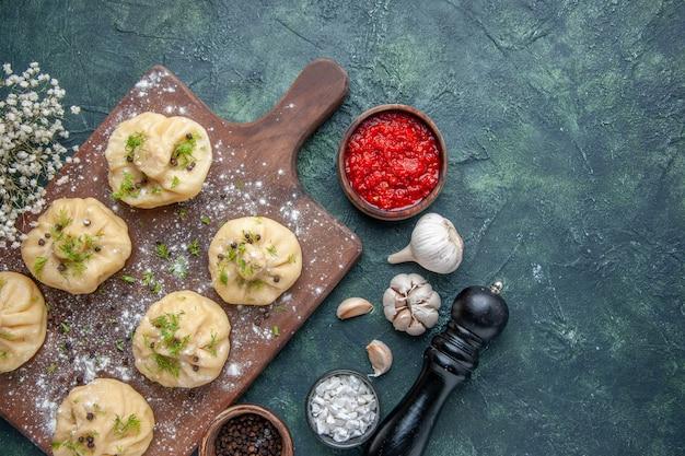 Vista dall'alto piccoli gnocchi crudi con salsa di pomodoro su sfondo blu scuro cena pasta di carne piatto torta pasto cucina cucina