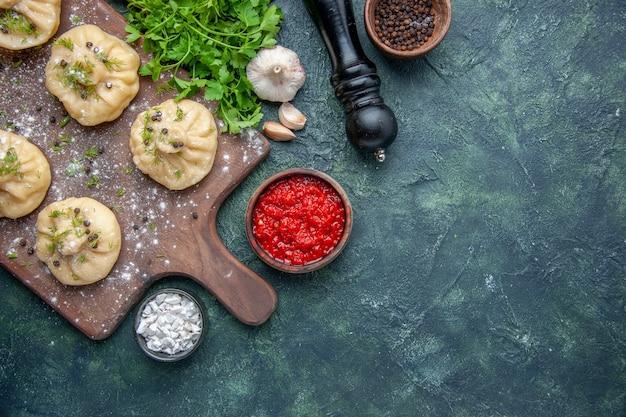 Vista dall'alto piccoli gnocchi crudi con salsa di pomodoro e verdure su sfondo blu scuro cucina cucina cena pasta piatto pasto carne