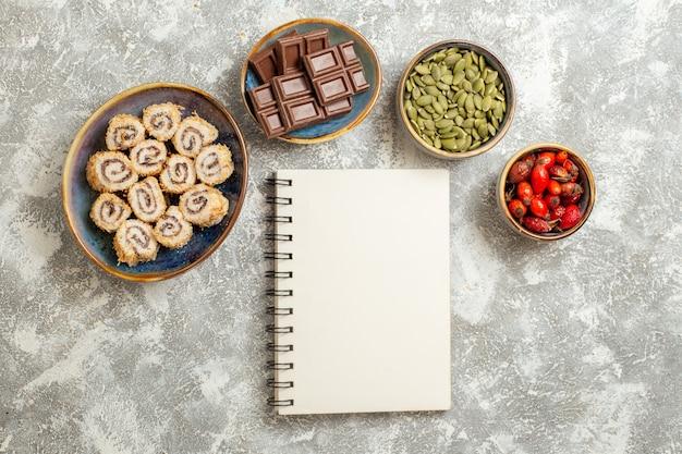 Vista dall'alto piccolo rotolo di caramelle con barrette di cioccolato su sfondo bianco