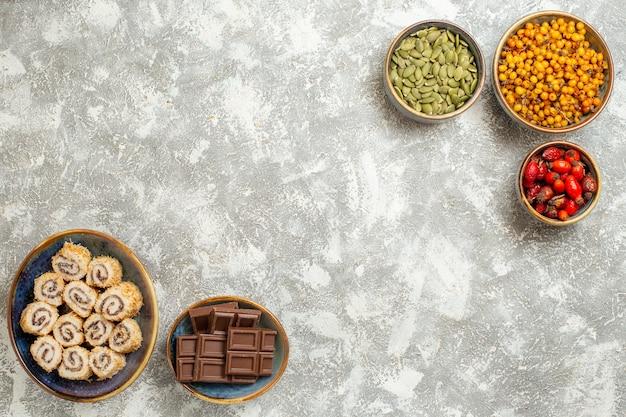 トップビューライトホワイトの背景にチョコレートと小さなロールキャンディー