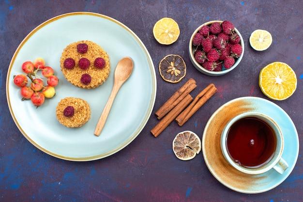 Vista dall'alto della piccola torta rotonda con lamponi freschi all'interno del piatto con tè alla cannella di frutta sulla superficie scura