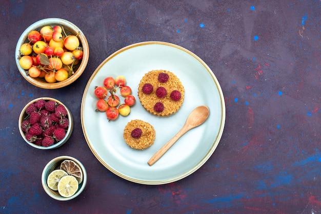 Vista dall'alto della piccola torta rotonda con lamponi freschi all'interno del piatto con frutti sulla superficie scura