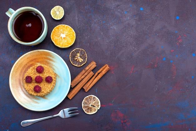 Vista dall'alto della piccola torta rotonda con lamponi freschi all'interno del piatto con tè sulla superficie blu scuro