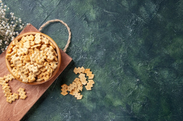 Vista dall'alto di piccoli cracker salati in ciotola su tavola di legno