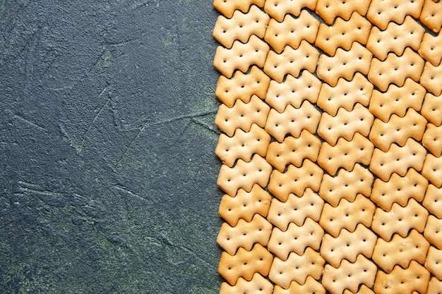 Top view of little salted crackers on dark surface