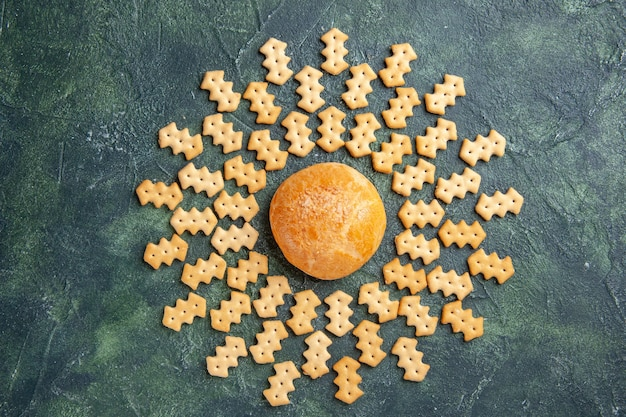 Top view of little salted crackers with little cake on dark surface