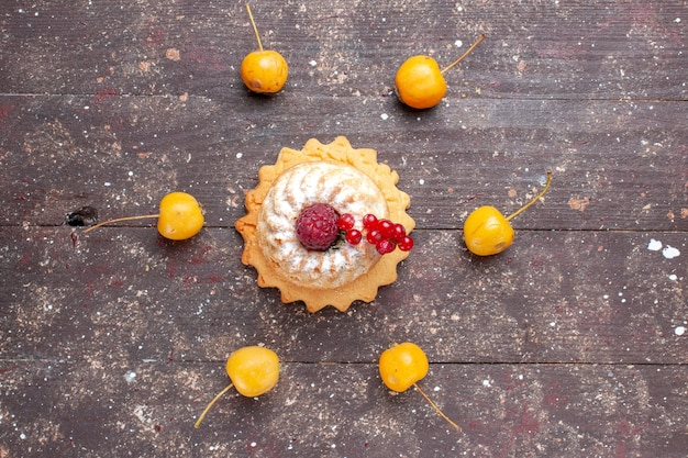 Вид сверху маленький простой торт с сахарной пудрой, малина и клюква, желтая вишня на коричневом деревянном деревенском фоне, ягодный фруктовый торт, сладкая выпечка