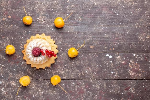 Вид сверху маленький простой торт с сахарной пудрой, малина и клюква, желтая вишня на коричневом деревянном деревенском столе, ягодный фруктовый торт, сладкая выпечка