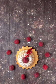Top view of little simple cake with sugar powder raspberry and cranberries on brown wooden,  berry fruit cake sweet bake