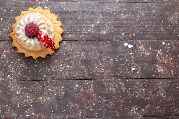 Top view little simple cake with sugar powder raspberry and cranberries on the wooden rustic background berry fruit cake sweet bake