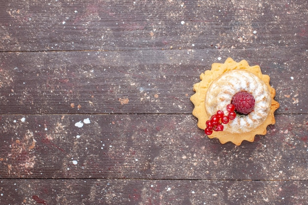 Top view little simple cake with sugar powder raspberry and cranberries on the wooden rustic desk berry fruit cake sweet