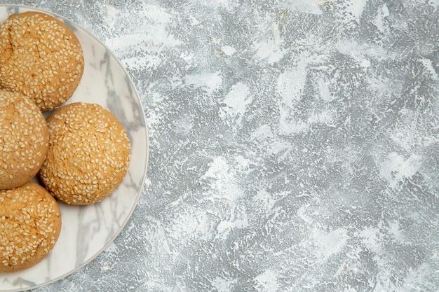 Вид сверху маленькое мягкое печенье вкусный десерт для чая внутри тарелки на белой поверхности