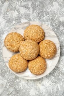 Vista dall'alto piccoli biscotti morbidi deliziosi dessert per il tè all'interno del piatto su superficie bianca