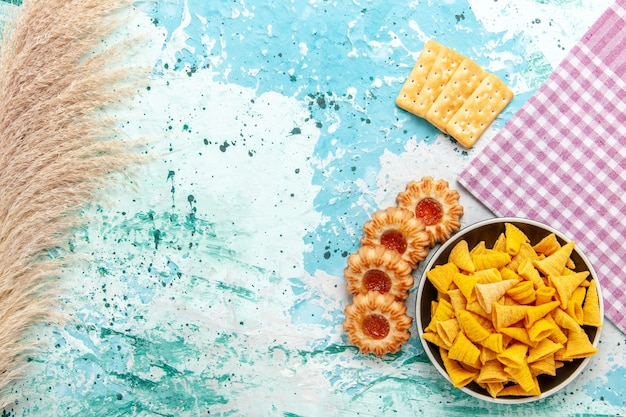 Vista dall'alto piccole patatine piccanti all'interno del piatto con cracker e biscotti su sfondo azzurro patatine fritte snack colore croccante caloria