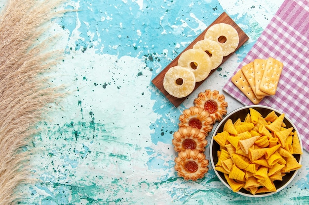 Top view little spicy chips with crackers dried pineapple rings and cookies on light-blue background chips snack color crisp calorie