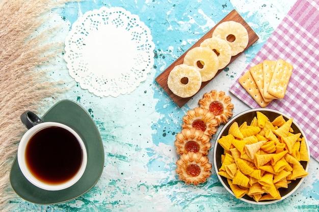 Vista dall'alto piccole patatine piccanti con cracker secchi anelli di ananas e biscotti su patatine fritte blu chiaro snack colore croccante caloria