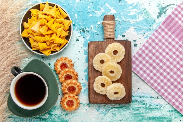 Top view little spicy chips with salted crackers and cookies on light blue surface cookie biscuit sweet sugar tea tea