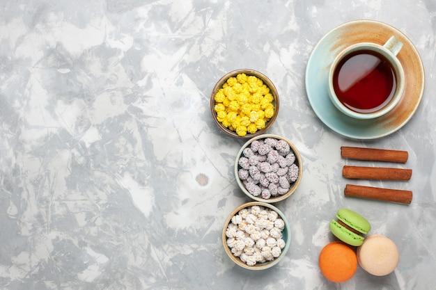 上面図白い背景の上のお茶とフレンチマカロンの小さな砂糖菓子ケーキビスケット茶甘い砂糖