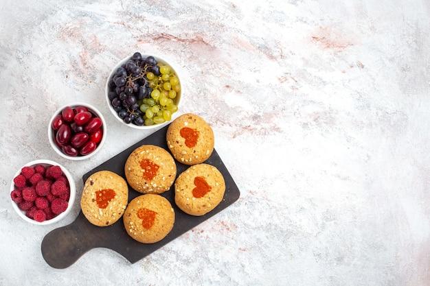 トップビュー小さなシュガークッキー白い背景の上の果物とお茶のためのおいしいお菓子パイクッキーシュガービスケット甘いケーキ