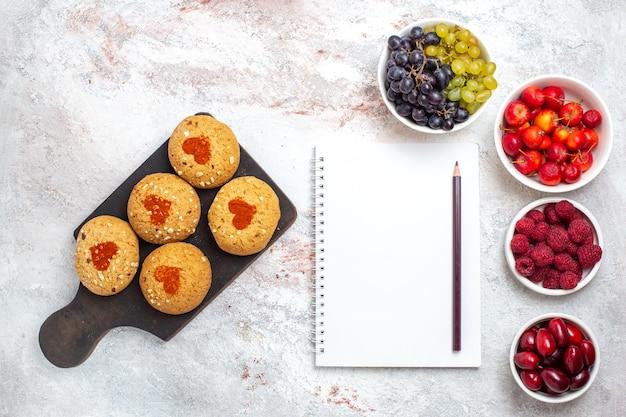 上面図小さなシュガークッキー白い表面に果物とお茶のためのおいしいお菓子パイクッキーシュガービスケットの甘いケーキ
