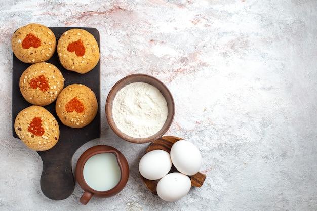 Vista dall'alto piccoli biscotti di zucchero deliziosi dolci per il tè con uova e latte sulla superficie bianca torta biscotto zucchero biscotto torta dolce