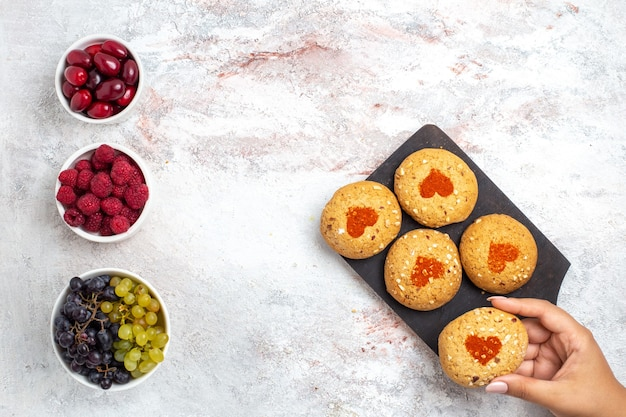 Vista dall'alto piccoli biscotti di zucchero deliziosi dolci per il tè con frutta sulla superficie bianca leggera torta biscotti zucchero torta dolce